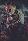 Polisman med gasmasken över explosionbakgrund Royaltyfria Bilder
