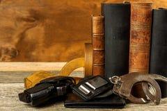Polisskrivbord Böcker av lagar och polishandbojor Utredning av brottet Vapen och lagar Lag och beställning royaltyfri fotografi