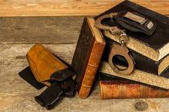 Polisskrivbord Böcker av lagar och polishandbojor Utredning av brottet Vapen och lagar Lag och beställning royaltyfri foto