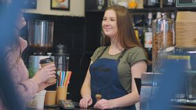 Polite barista fulfills order giving coffee cup to client