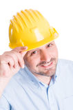 Polite engineer or architect touching helmet Stock Images