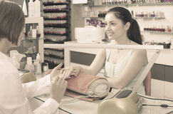 Polite female manicurist filing and shaping nails in beauty salo Stock Images