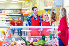 Polite grocery staff serves customer in the mall Royalty Free Stock Photos