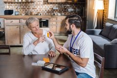 Polite kind volunteer persuading an old man to take his pills Royalty Free Stock Photography