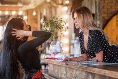 Polite receptionist woman with a smile meets customer indoors, hotel, Studio or salon royalty free stock images