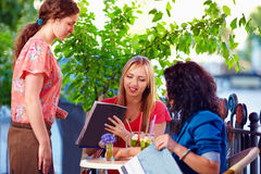 Polite waitress serving clients on summer cafe terrace Stock Image