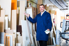 Polite workman standing with plywood pieces Royalty Free Stock Image