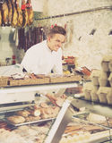 Polite young seller offering fresh products. Polite young seller at butcher store offering fresh products Stock Photo