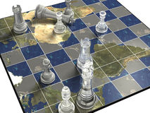 Political Chess. Clear and solid chess pieces on a chess board inlaid with world continents Royalty Free Stock Photo
