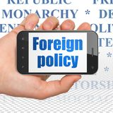 Political concept: Hand Holding Smartphone with Foreign Policy on display. Political concept: Hand Holding Smartphone with  blue text Foreign Policy on display Stock Photos