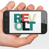 Political concept: Hand Holding Smartphone with Revolt on  display. Political concept: Hand Holding Smartphone with Painted multicolor text Revolt on display, 3D Royalty Free Stock Photos