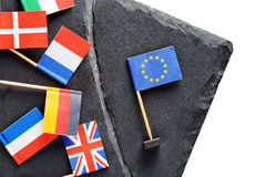 Political concept with small flags of the European Union. Flags of European countries separated by crack from flag of the European Union Royalty Free Stock Photos