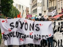 Political march during a French Nationwide day against Macrow la. STRASBOURG, FRANCE - SEPT 12, 2017: Masked people with Soyons Revolutionnaires translated as Be Royalty Free Stock Photos