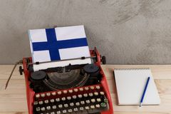 Political news and education concept - red typewriter, flag of the Finland, notebook on gray cement background. Political, news and education concept - red stock photos