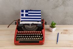 Political, news and education concept - red vintage typewriter, flag of the Greece, pencil royalty free stock photo