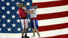 Political parties choking against American Flag. Man in elephant GOP mask and woman in donkey Democrat mask wearing boxing shorts choking each other against stock video footage