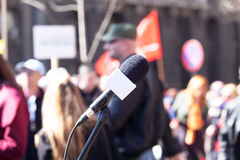 Political protest. Demonstration. Microphone in focus, blurred protesters in background. Royalty Free Stock Photo