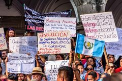 Political protests, Antigua, Guatemala. Antigua, Guatemala - September 15, 2017: Locals wave Guatemalan flags & slogans protesting against government corruption royalty free stock photography