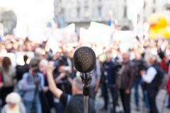 Political rally. Protest. Demonstration. Microphone in focus, blurred crowd in background Royalty Free Stock Image