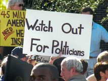 Political Rally with protest sign stating `Watch Out for Politicians`. Political Rally with large white protest sign stating `Watch Out for Politicians royalty free stock photography