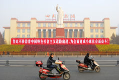Political slogan in china. Two men riding a motorcycle pass by a chinese political slogan, and Mao Zedong statue at Tian-fu Square in Chengdu, China stock image
