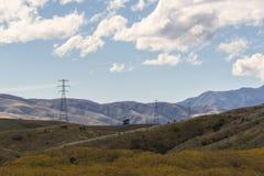 Politici elettrici ad alta tensione nella catena montuosa Fotografia Stock Libera da Diritti