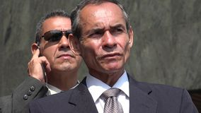 Politician With Bodyguard. Older and hispanic business men royalty free stock photos