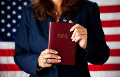 Politician: Holding a Bible. Series with an adult female in a suit, playing the part of a United States politician.  Different props provide a variety of Stock Image