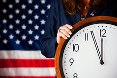 Politician: Holding a Clock. Series with an adult female in a suit, playing the part of a United States politician.  Different props provide a variety of Stock Photo