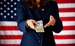 Politician: Holding a Stack of Cash. Series with an adult female in a suit, playing the part of a United States politician.  Different props provide a variety of Stock Photos
