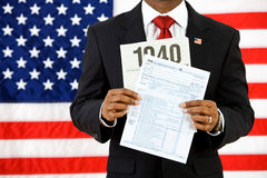 Politician: Holding Up the US Income Tax Form Royalty Free Stock Image