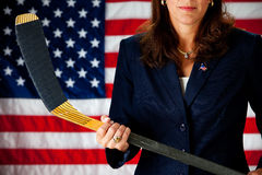 Politician: Politician as Hockey Mom. Series with an adult female in a suit, playing the part of a United States politician.  Different props provide a variety Royalty Free Stock Photography