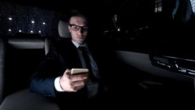 Politician using phone on back seat of luxury car as driving home, workaholic royalty free stock image