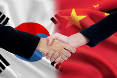 Politicians handshake with chinese and south korean flags Stock Photos