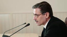 Politicien à une conférence de presse Vérifie le microphone et salue l'assistance, vue de côté clips vidéos