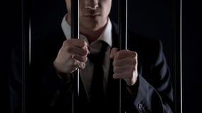 Politicien tenant des barres de prison, mâle officiel arrêté sur le blanchiment d'argent photographie stock libre de droits