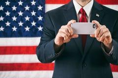 Politicien : Utilisant un téléphone portable comme appareil-photo image stock