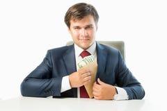 Politicien vénal mettant l'argent dans l'enveloppe dans la poche de son costume images stock