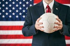 Politico: Pallone da calcio della tenuta dell'uomo Fotografie Stock