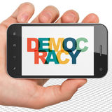 Politics concept: Hand Holding Smartphone with Democracy on  display Royalty Free Stock Images