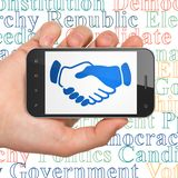 Politics concept: Hand Holding Smartphone with Handshake on display. Politics concept: Hand Holding Smartphone with  blue Handshake icon on display,  Tag Cloud Stock Photography