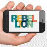 Politics concept: Hand Holding Smartphone with Rebellion on  display. Politics concept: Hand Holding Smartphone with Painted multicolor text Rebellion on display Royalty Free Stock Photography