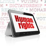 Politics concept: Tablet Computer with Human Rights on display. Politics concept: Tablet Computer with  red text Human Rights on display,  Tag Cloud background Stock Photography