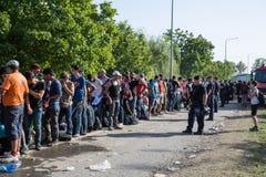 Politie die de wachtende lijn van Vluchtelingen in Tovarnik bewaken Stock Fotografie