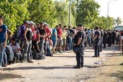 Politie die de wachtende lijn van Vluchtelingen in Tovarnik bewaken Royalty-vrije Stock Afbeelding