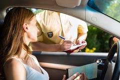 Politie - vrouw in verkeersschending die kaartje krijgt Stock Afbeeldingen
