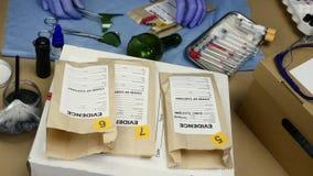 Politie Wetenschappelijke die het onderzoeken bewijsmateriaalzak in ballistisch laboratorium wordt geëtiketteerd stock footage
