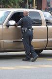Politieagent die auto's controleert stock afbeelding
