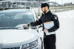 Politieagent die boete op de auto zetten royalty-vrije stock afbeeldingen