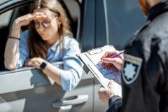 Politieagent die een boete voor een vrouwelijke bestuurder uitgeven royalty-vrije stock afbeelding